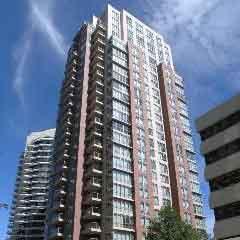 high rise condo building sky blue clouds
